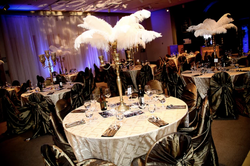 The dining hall had cream and gold tablecloths, dark henna green wrap chair covers, gold candelabras with ostrich feathers, paisley print gobo lighting on the focal wall and purple uplighting throughout the room.