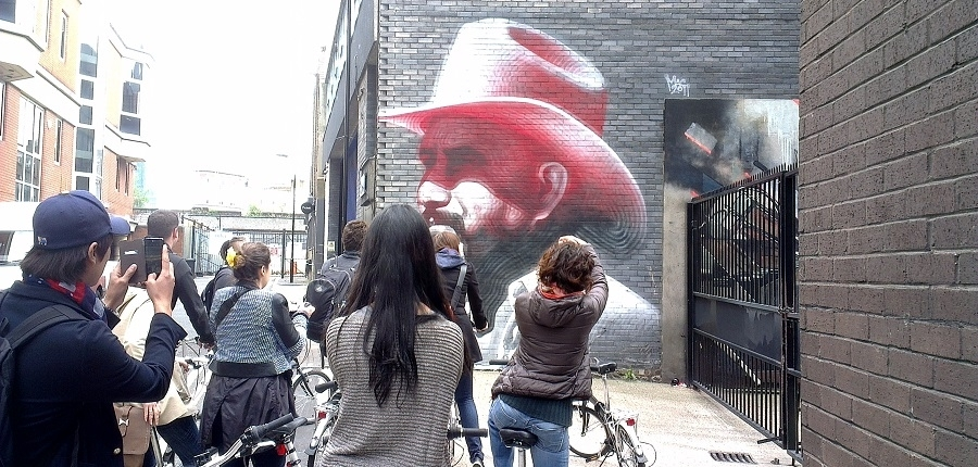 Alternative London Bike Tours are the best way to explore the neighborhood. Here, cyclists capture photos of artwork by El Mac. Image: Alternative London. Artwork: El Mac.