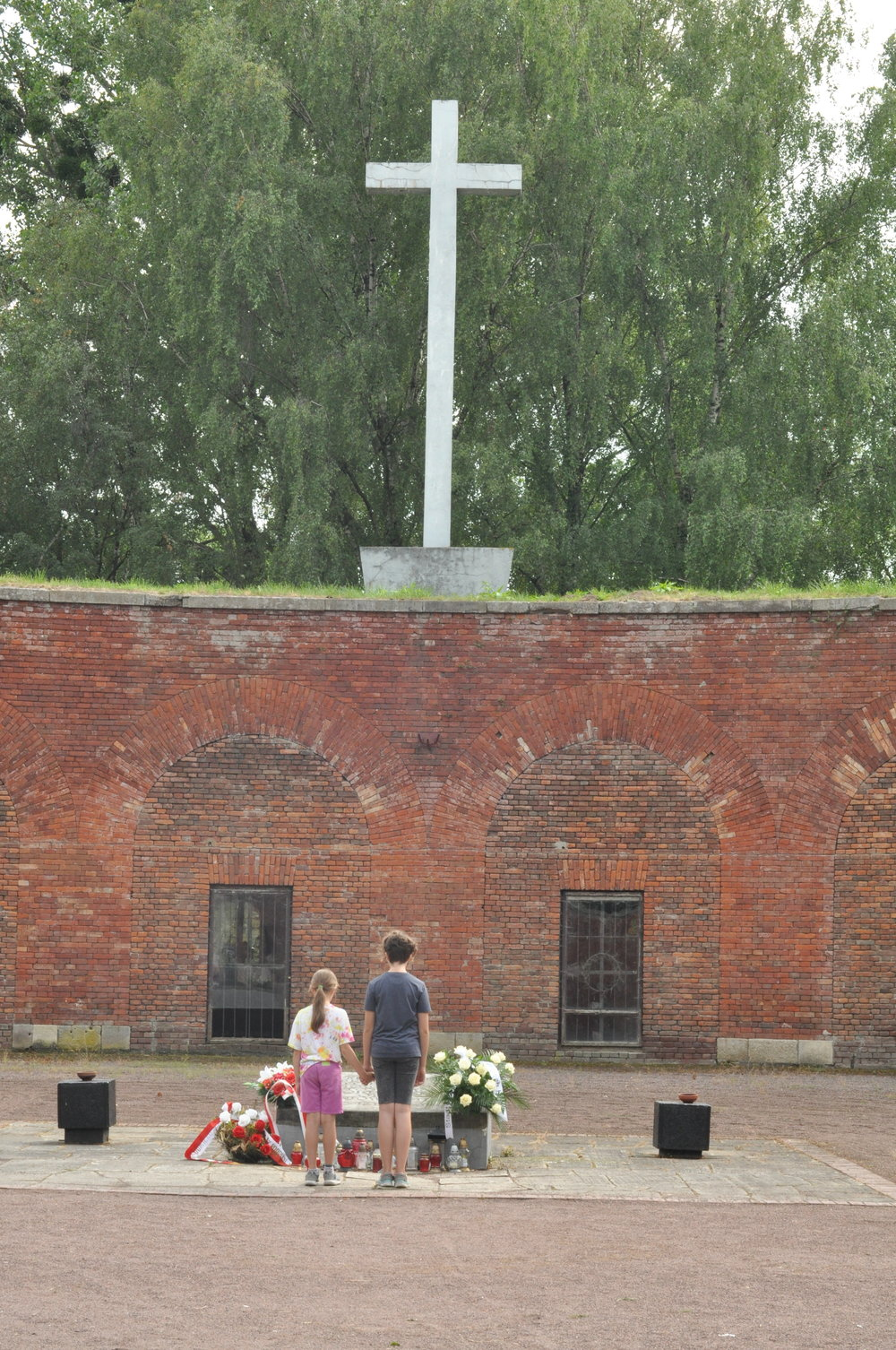 Two children pay their respects at the Rotunda in Zamosc, Poland
