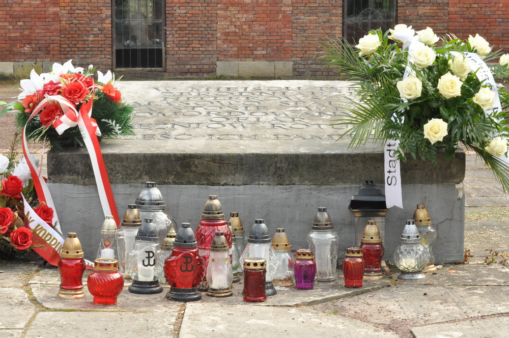 Flowers and candles surround the plaque commemorating those whose bodies were burned in the Rotunda in Zamosc, Poland during World War II.