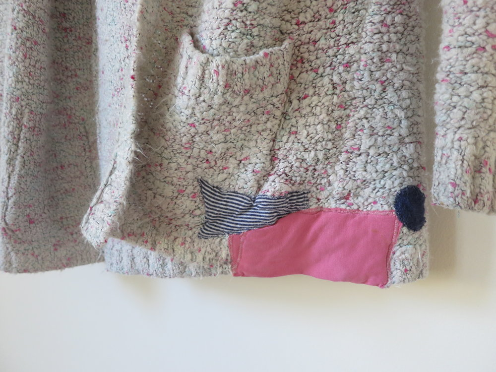 Visible mending on a sweater