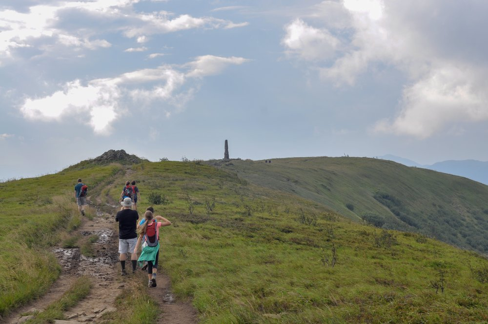 Hikers approaching the monument at Wielka Rawka on the Tri-Border hike in the Bieszcady Mountains