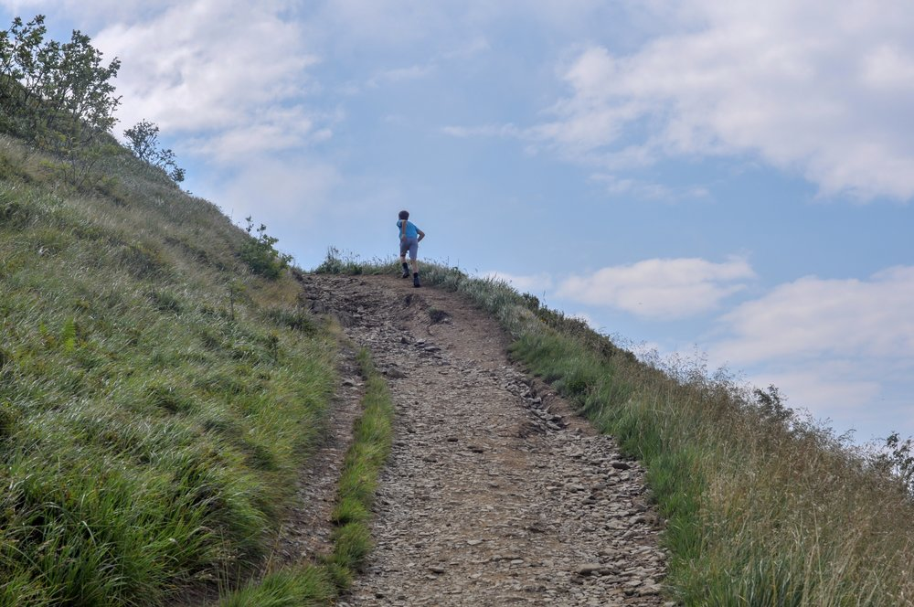 A boy runs up a hill on the trail to the Tri-Border area in the Bieszczady Mountains