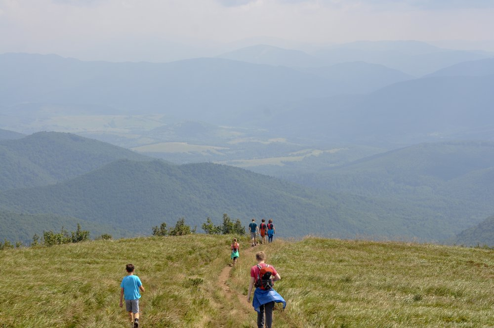Hikers walking through the połoniny on the Tri-Border hike in the Bieszcady Mountains