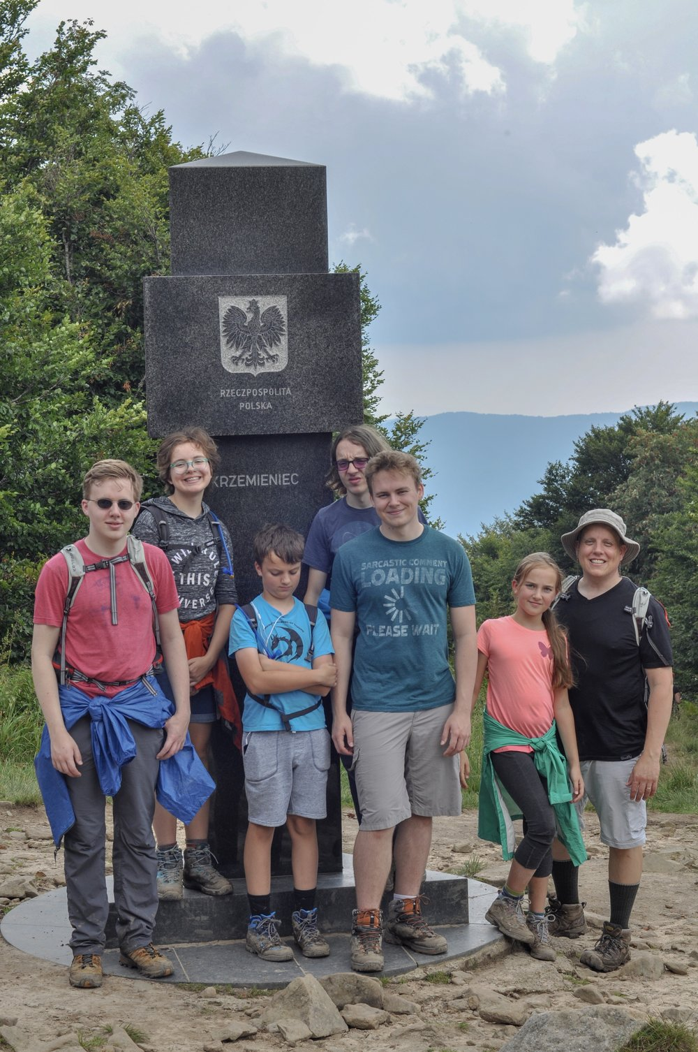 Hikers at the tri-border marker at the Poland-Ukraine-Slovakia border in the Bieszcady Mountains