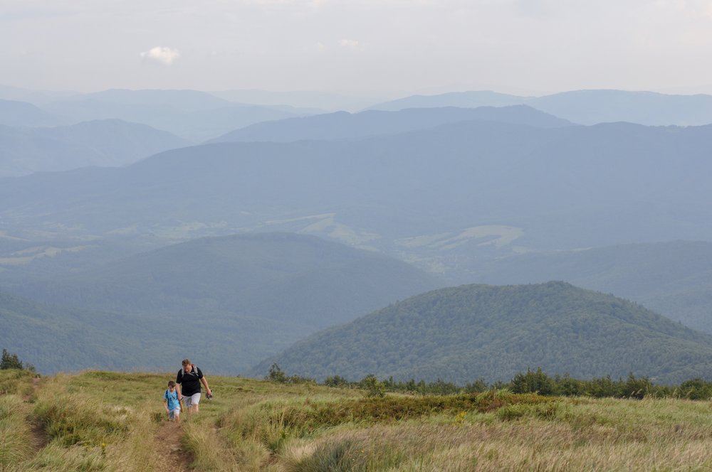 Two hikers walking through the połoniny on the Tri-Border hike in the Bieszcady Mountains