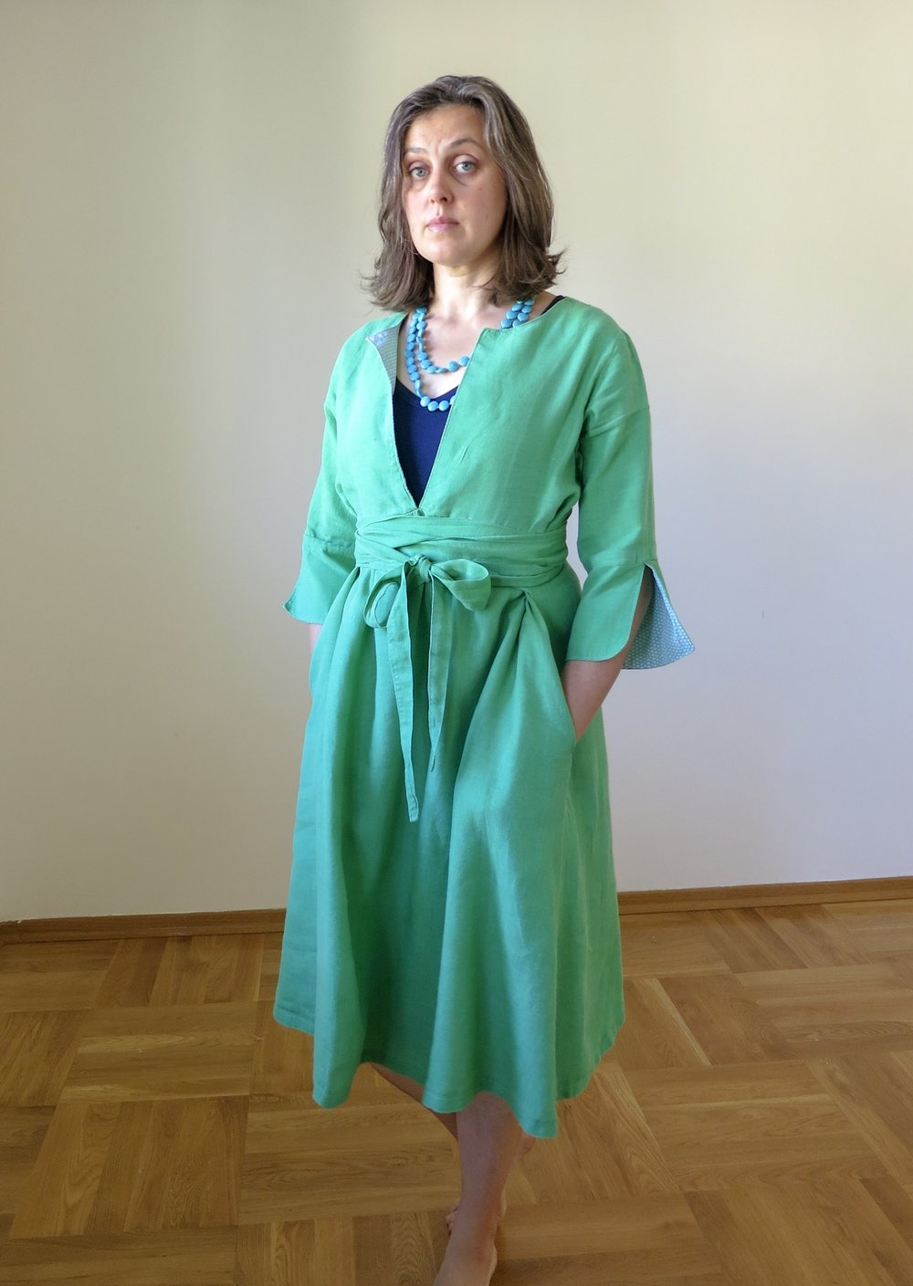 Schoolhouse Tunic pattern turned into a dress with ties and pockets in green linen