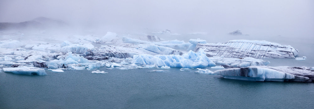 Jokulsarlon glaciers are covered in clouds during a cold and wet afternoon.