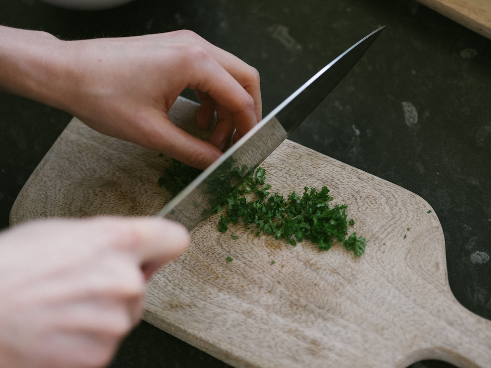 Chop fresh parsley for the filling and garnishing of the eggs.