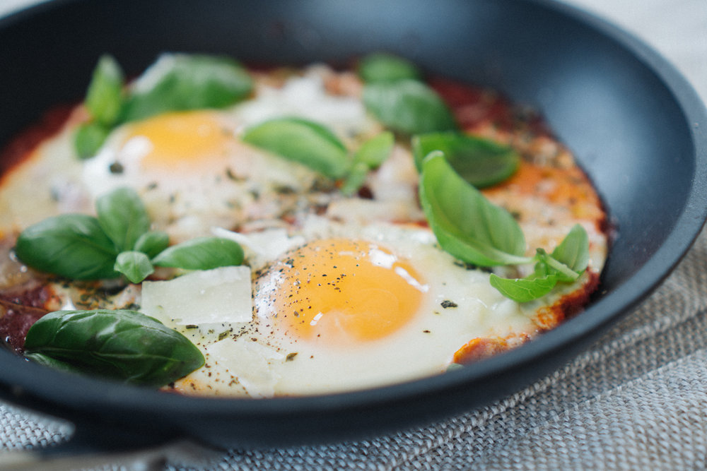 The yolks should stay nice and runny. Garnish with some parmesan cheese, lots of fresh basil and here's your shakshuka.