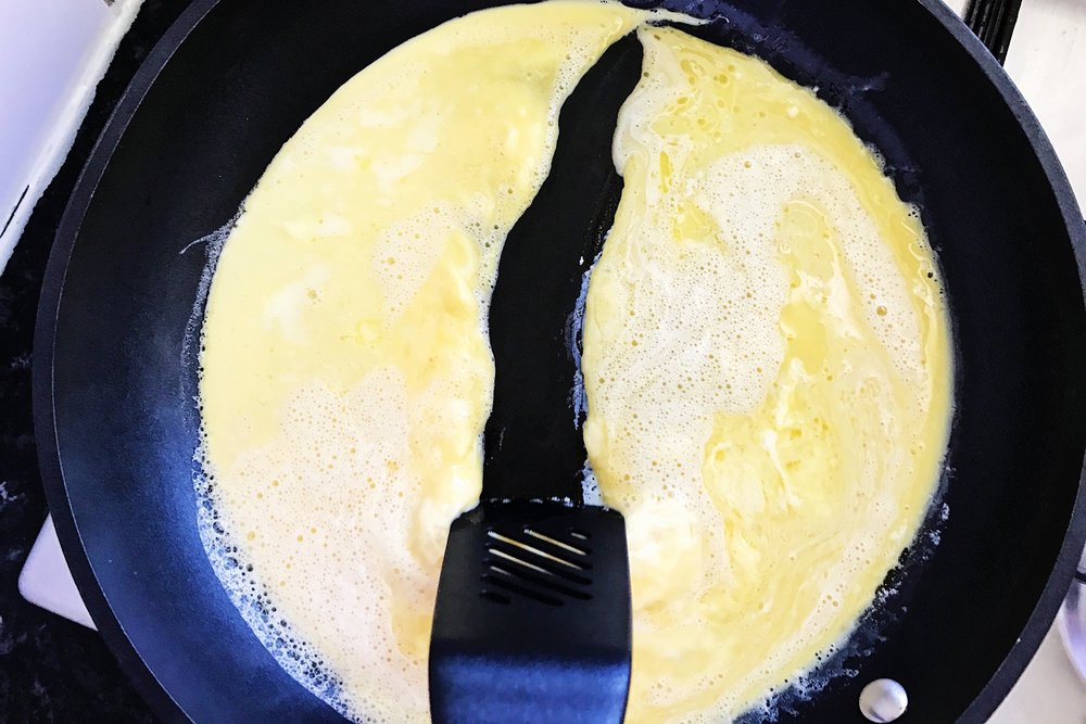 Once there's a thin layer of set eggs on the bottom, start softly scraping and pushing the eggs towards the middle of the pan and across it.