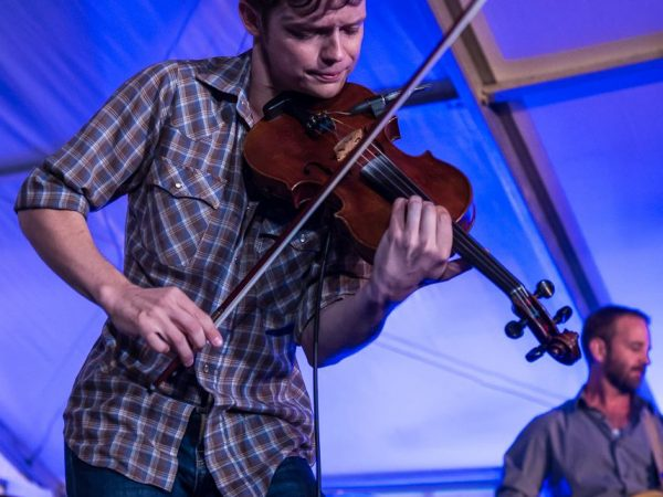DMi is proud to sponsor   WARREN HOOD     7:00 pm  June 3, 2017    Warren Hood hails from the fertile musical grounds of Austin, Texas. The son of music legend Champ Hood, Warren began playing the violin at eleven, and graduated with honors from the Berklee College of Music. Warren became recognized as a  virtuosic fiddler , and as an accomplished multi-instrumentalist, songwriter, and singer as a founding member of the South Austin Jug Band. Warren has been recognized three times as String Player of the Year in the Austin Chronicle Music Awards. Warren tours extensively with the Waybacks and the BoDeans. He has also performed and/or recorded with Lyle Lovett, Ben Kweller, Little Feet, Elvis Costello, and Alejandro Escovedo. The Warren Hood Band features Warren Hood on fiddle and vocals, Austin guitar ace Willie Pipkin, and award-winning pianist and vocalist Emily Gimble, granddaughter of the legendary Texas fiddler Johnny Gimble, as well as bass and drums. Warren Hood can also appear as a solo and duo artist.