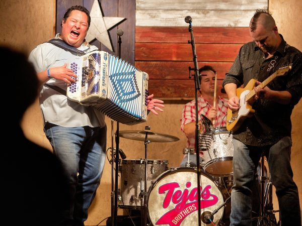 "DMi is proud to sponsor TEJAS BROTHERS 7:00 pm  August 12, 2017  When rock 'n' roll meets Tex-Mex in a honky tonk that is home to the blues, you get the Tejas Brothers. This quartet absolutely disregards any notions of staying within a certain ""genre."" If it feels good, and makes people happy, it ought to be a Tejas Brothers song. Shows are family-friendly and focus on the idea that we only live once, and we should all get the most out of life. In 2013, the Dallas Observer Music Awards named the Tejas Brothers ""Best Country Act."" Their latest CD, ""Live a Little More,"" was produced by Lloyd Maines. In 2009, they had the #7 album on the Americana Radio Airplay Charts. The Tejas Brothers is a four-piece band comprising accordion, upright bass, guitar, and drums. Shows can be acoustic or electric, and up to two hours in length. The Tejas Brothers' repertoire of original and cover songs include: Boogie Woogie Mamacita (original); I Can't Sleep (original); Don't Be So Mean (original); Seven Spanish Angels; Hey Baby Que Paso; Crying Time; and El Sapito"