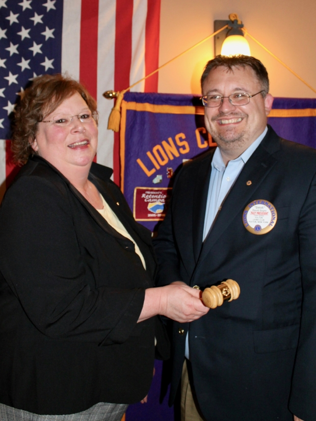 David Guyer, who completed his second term as president of the Fulton Lions Club, hands the club gavel to Michelle Stanard, president for the 2017-18 year.