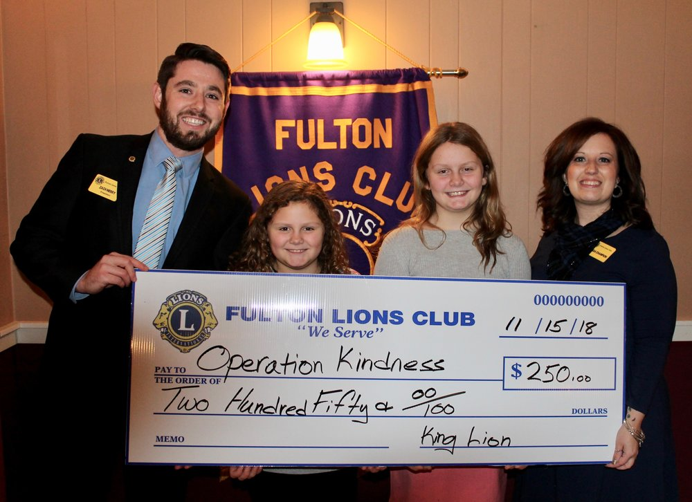 The Fulton Lions Club made a $250 donation to Operation Kindness, the brainchild of Autumn Barrick, a 5th grade student at Lanigan Elementary, second from right. Operation Kindness, now in its second year, provides Christmas toys and gifts at no charge to those who need them. It runs from 9:00 a.m. to 4:00 p.m. on Sat., Dec. 1, in the community room of the Fulton Municipal Building, 141 S. First St. Each shopper may take two new/gently used gifts for each child in their home. In addition to toys, there will be free drawings for popular toys, and there are also some winter coats available. Joining Autumn were, from left: Zachary Merry, Fulton Lions president; her sister, Addison Barrick; and Lion Melissa Champion, who brought the program to the Lions club. For further information, contact Nichole Slocum at slocumnichole@gmail.com.
