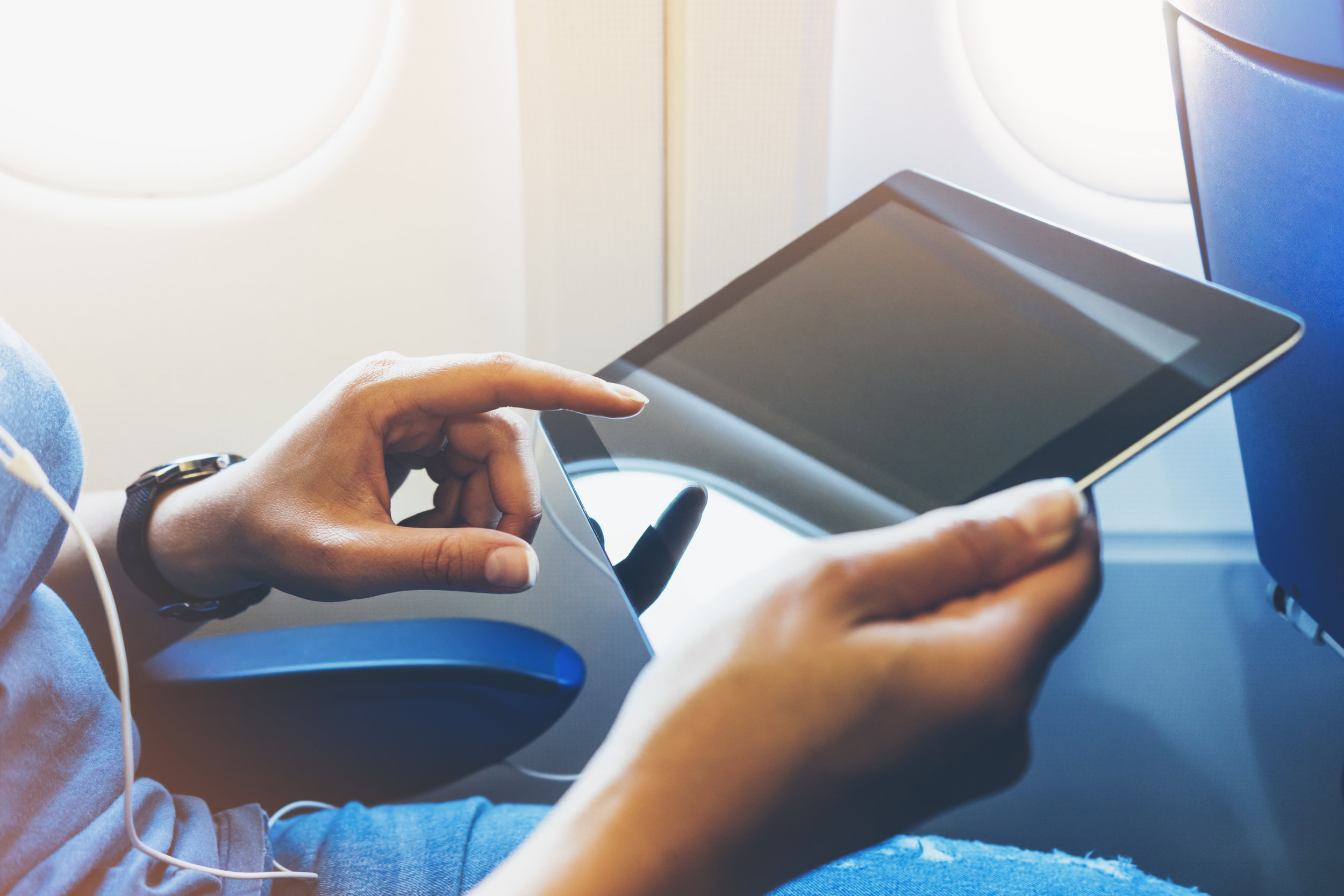 Side view of passenger traveler tourist using tablet at salon airplane. Female hands texting message on gadget on background window aircraft, summer traveler journey trip concept, mockup blank screen computer with flare
