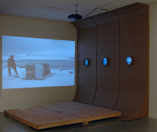 "CHAD STAYROOK    The Search for the unattainable beast... , digital projector, LCD monitors, DVD players, cardborad and wood 120"" x 120 x 120"", 2010"
