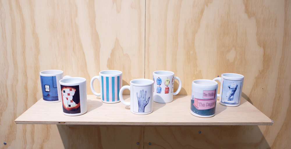 "Erik Scollon Shelf #2, 2018 7 individual handmade porcelain mugs with artist made ceramic decals, glaze and wooden shelf, 6"" x 32"" x 11"""