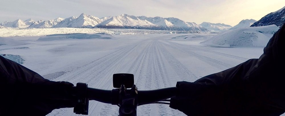 mountain and glacier view from behind fat tire bike handlebars