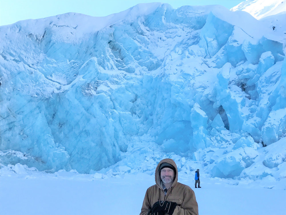 Man stands in front of Knik Glacier in winter