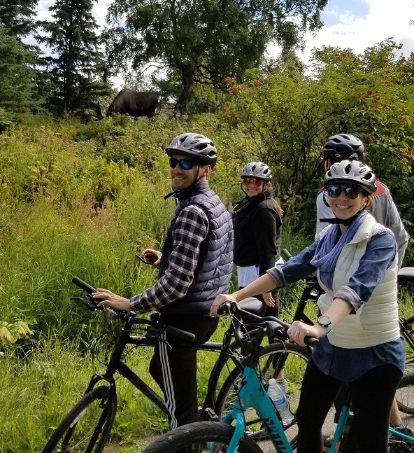 Happy bike tour group looking at moose Anchorage