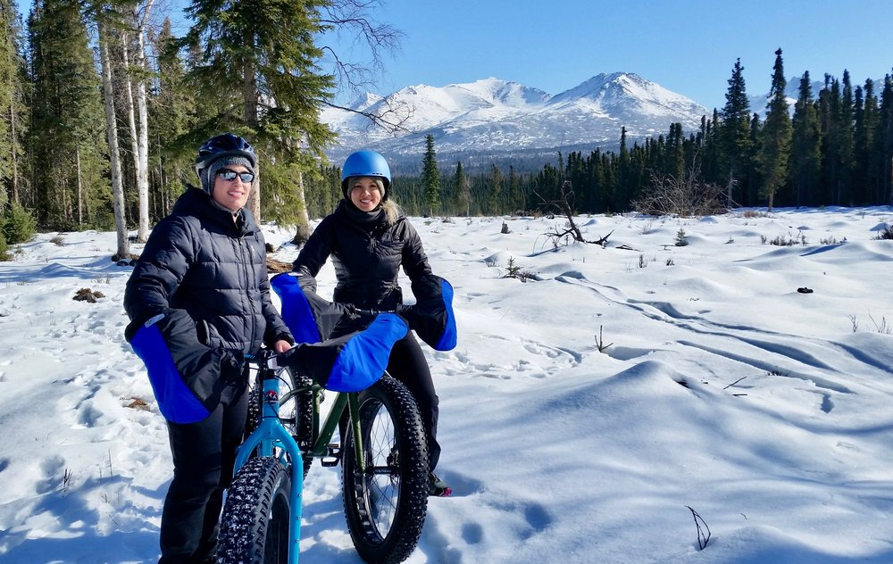 Happy fat tire bike tour group with winter mountain view