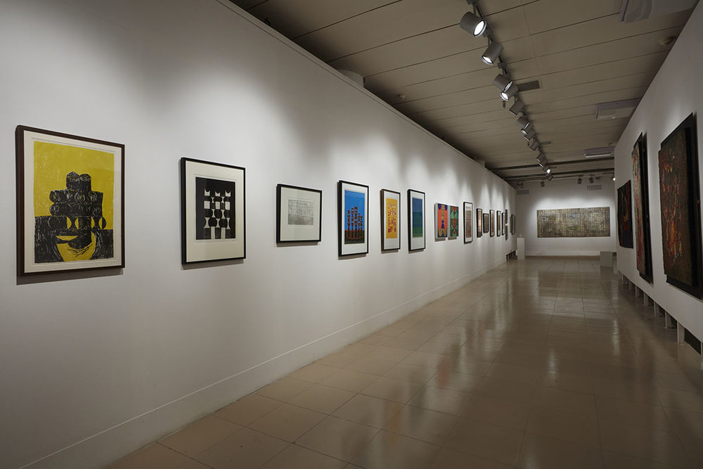 Installation view, works by Anwar Jalal Shemza (left). Courtesy of Jhaveri Contemporary, Mumbai and the Estate of Anwar Jalal Shemza, Eastbourne, UK, Rashid Choudhury (right). Courtesy of the Bangladesh National Museum, Bangladesh Shilpakala Academy, Anwar Hossain Manju Collection, Dhaka and Farooq Sobhan Collection, Dhaka and Zahoor Ul Akhlaq (back), courtesy of the Inayat Ismail Collection, Karachi, the Estate of Zahoor Ul Akhlaq, Lahore and Toronto, Jhaveri Contemporary, Mumbai and the Pakistan High Commission, Dhaka. Photo courtesy of the Dhaka Art Summit and Samdani Art Foundation. Photo credit: Jenni Carter