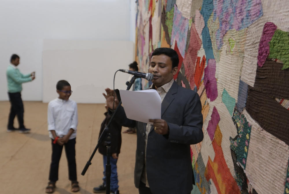 A member of the Bengali Migrant Poetry Forum presenting their words along with other members