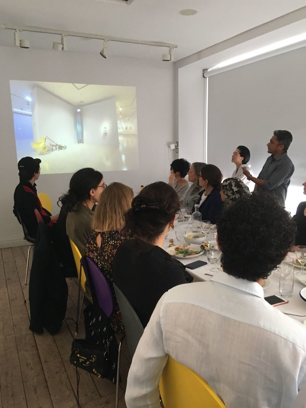 Mizanur Rahman Chowdhury giving a presentation on his work during a Delfina Foundation dinner. Image courtesy of Chowdhury.