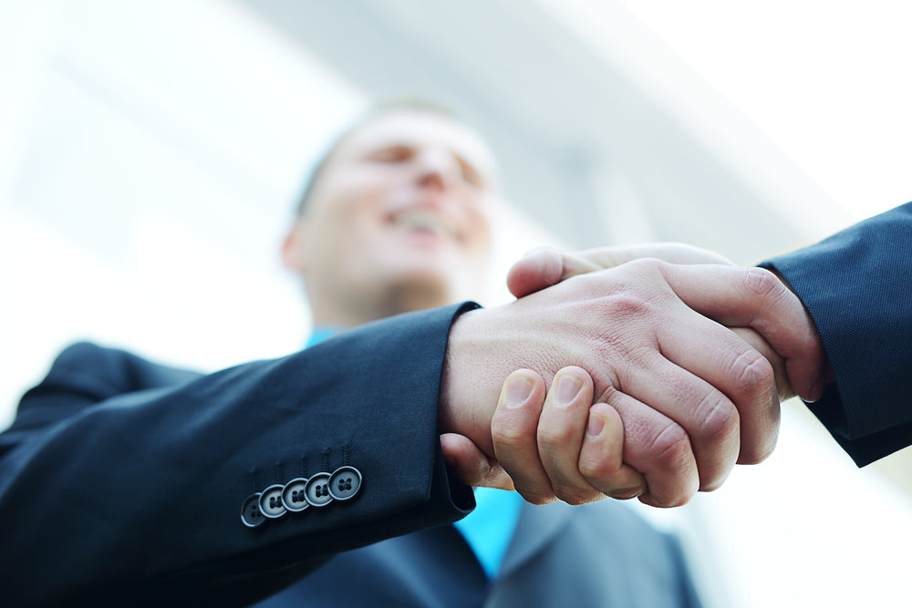 business-shaking-hands-in-front-of-modern-building-with-copy-space-selective-focus_BFQDWQ0Vj.jpg