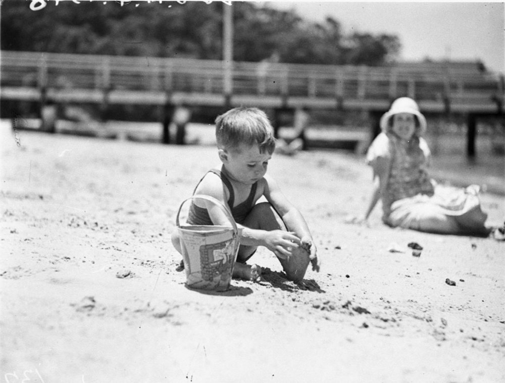 SLNSW_43355_Boy_playing_with_bucket_in_the_sand_at_the_Mick_Simmons_Radio_Club_picnic.jpg
