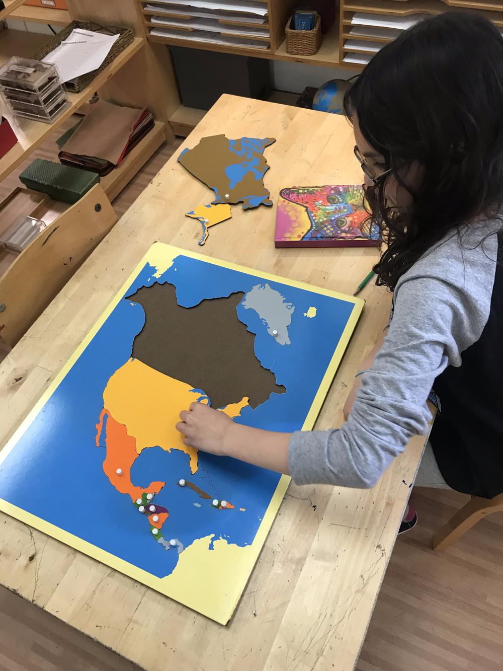 Child with a Montessori Puzzle Map (of North America)