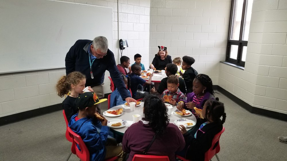 Our students and Teacher of the Month also get to eat pizza with the Principal. Mr. McCarthy is seen handing out pizza and drinks to our students for April.