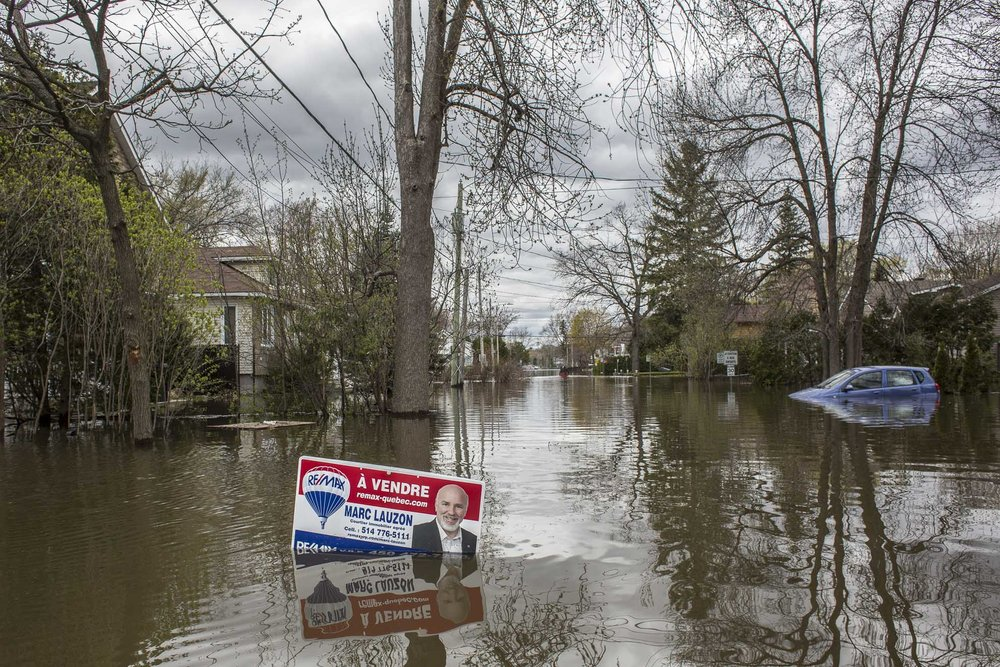 May 09, 2017 - Deux-Montagnes, Quebec, Canada: A sign for sale stand in the middle of a flooded street.(Normand Blouin/Polaris)