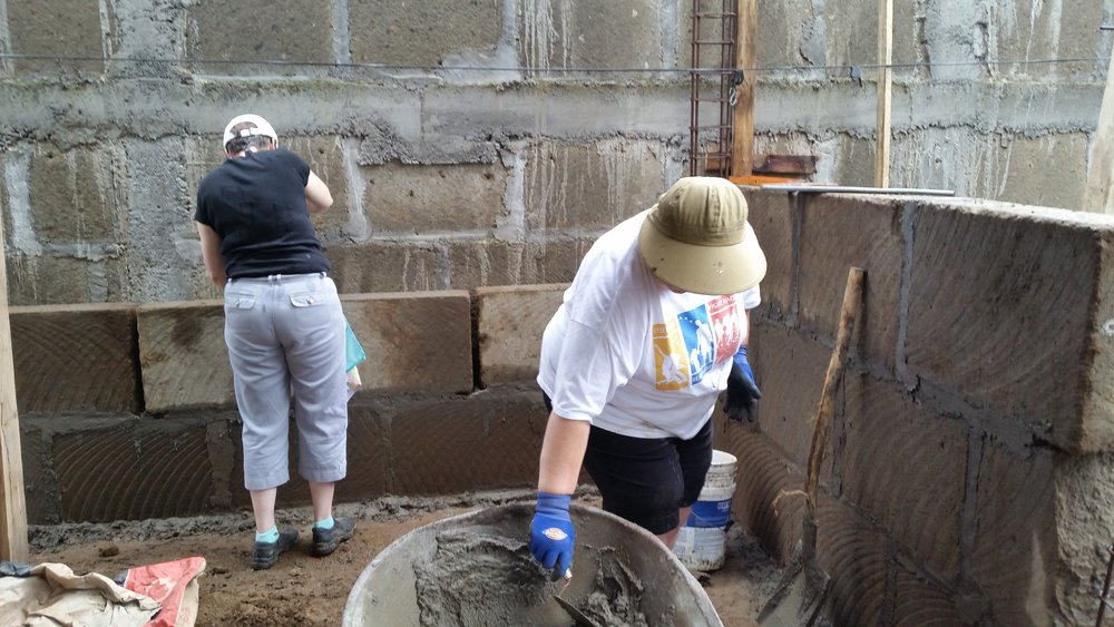 Janet and Geraldine place mortar between the blocks.
