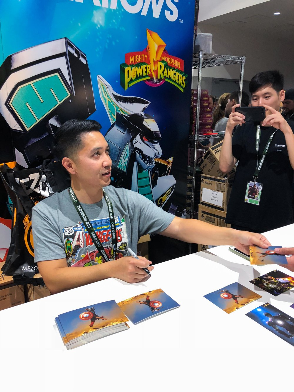 Signing and giving out photos at the Bluefin/Tamashii Nations booth at SDCC. Courtesy  @swittpics