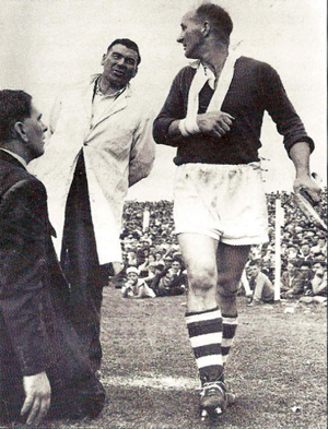 30th June 1957. The Munster semi-final between Cork and Tipperary at Limerick which Cork won by 5-2 to1-11. In the second half Christy Ring went off with a broken wrist. Mick Mackey. who was doing umpire for referee Mick Hayes of Clare, says something to Christy Ring as he leaves the field.