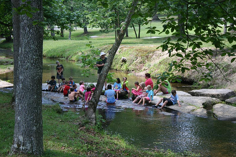 Summer Campers playing in the creek - NaCoMe Camp & Conference Center