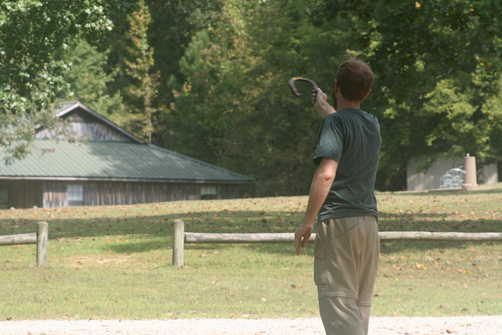 An adult Summer Camper playing horse shoes - NaCoMe Camp & Conference Center