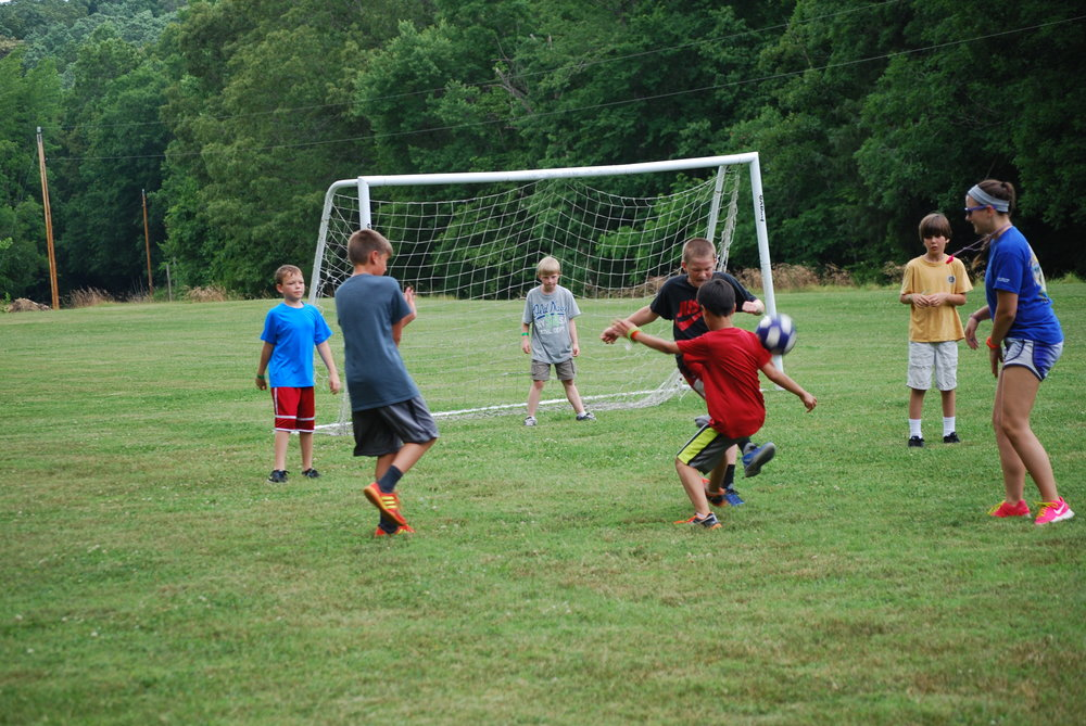 Young male Summer Campers playing soccer - NaCoMe Camp & Conference Center