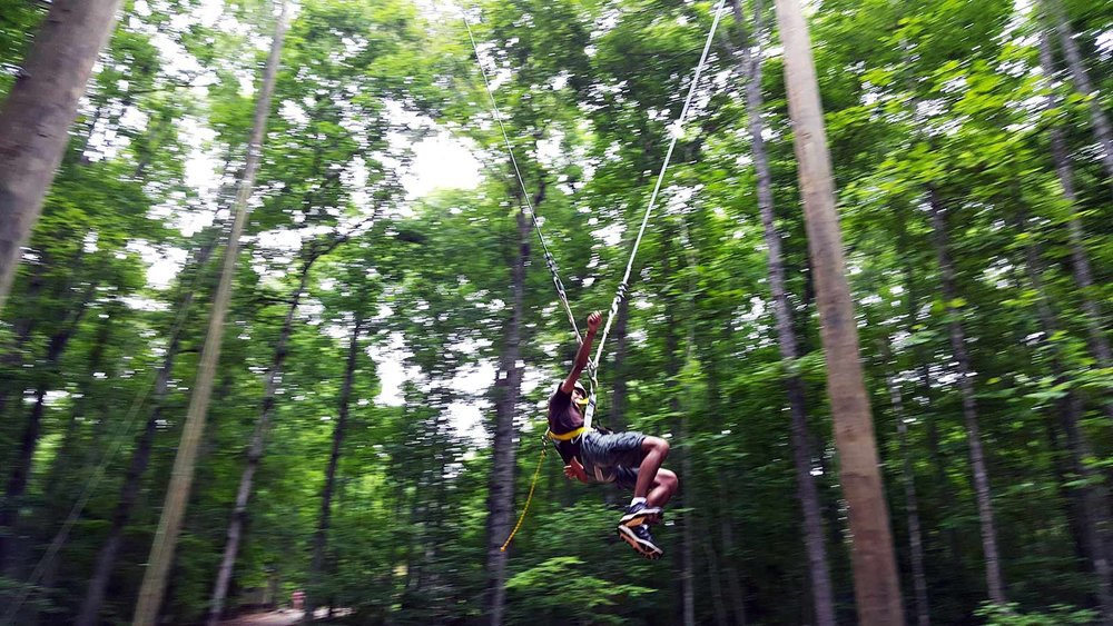 Summer Camper on the zip line in motion - NaCoMe Camp & Conference Center