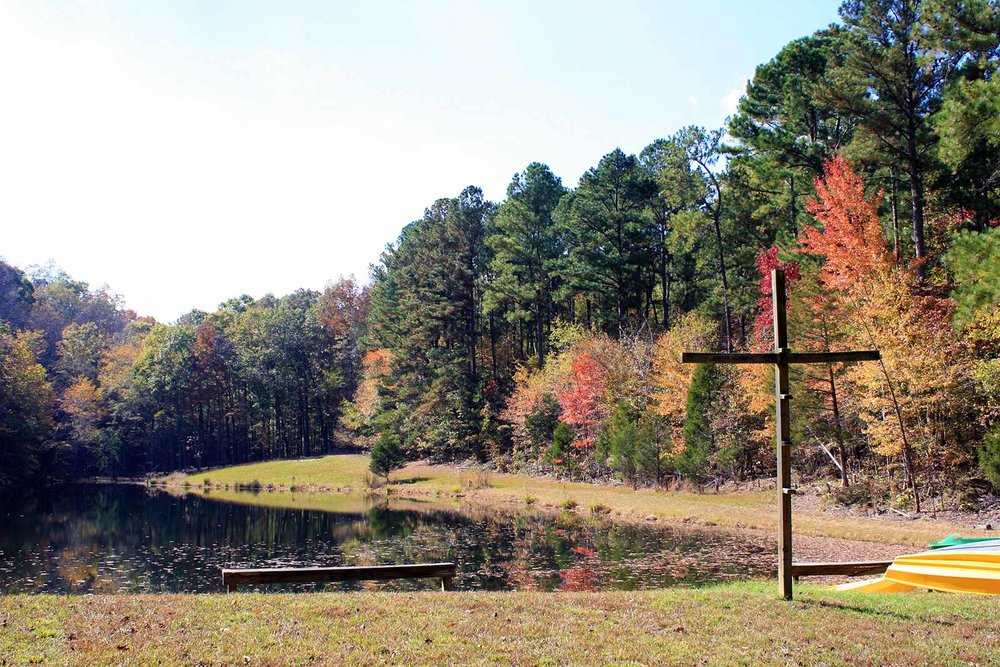 Copy of A beautiful new of the trees turning colors by a lake with calm water - NaCoMe Camp & Conference Center