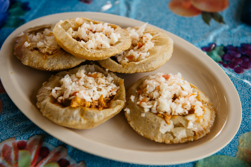 Salbutes: A corn tortilla that puffs when fried, then popped open and filled with recado-spiced meat, cabbage, and cheese