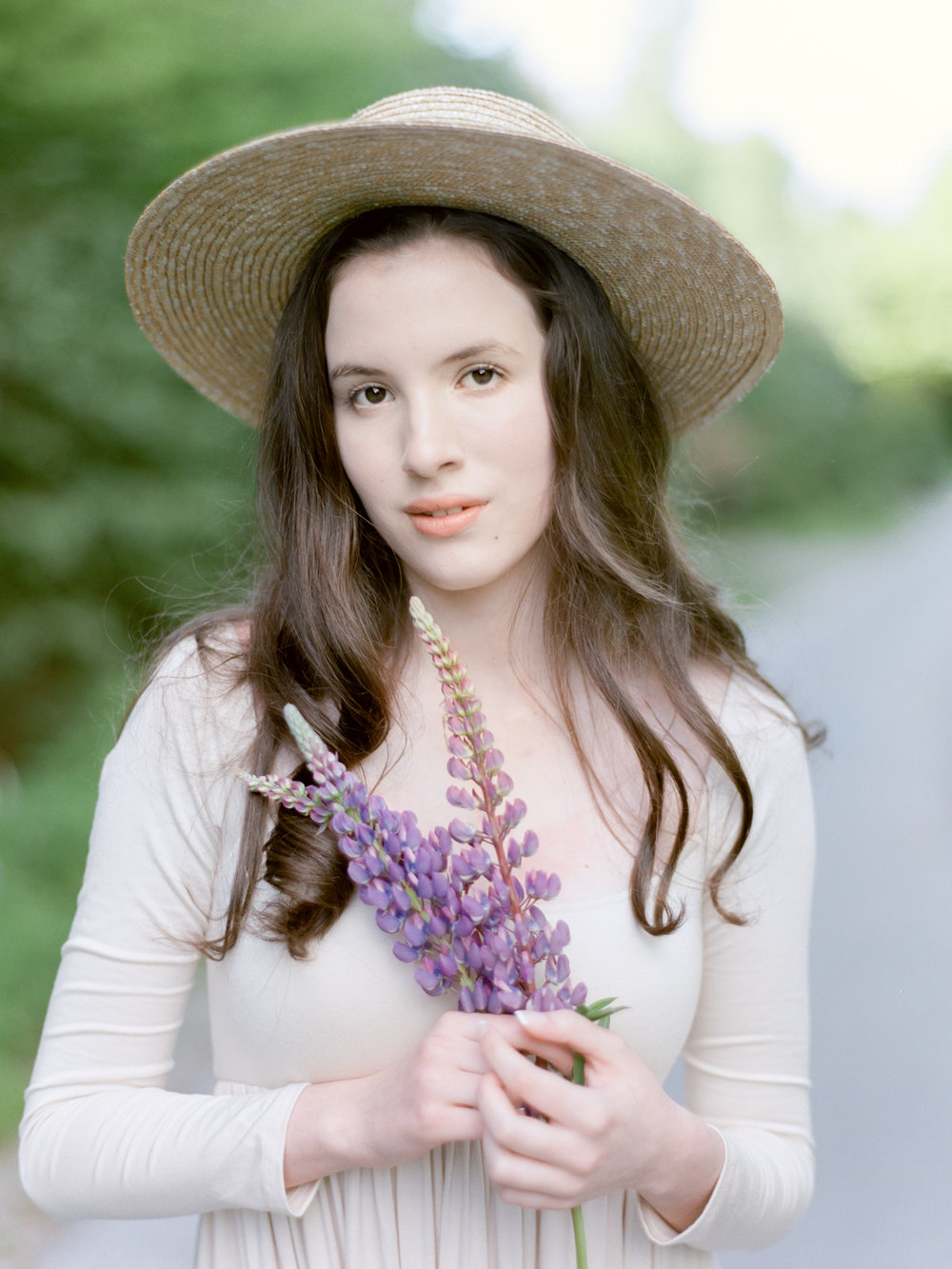 Jacqueline Anne Photography Captured on Film, Woman in cream dress and sunhat holding purple lupine florals