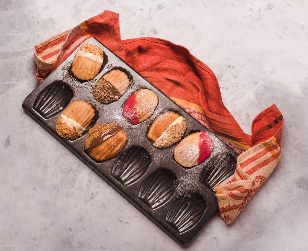 Buttery French Madeleine Cakes, coated in a Strawberry Glaze, Rich Milk or White Chocolate, and topped with Crushed Almonds.