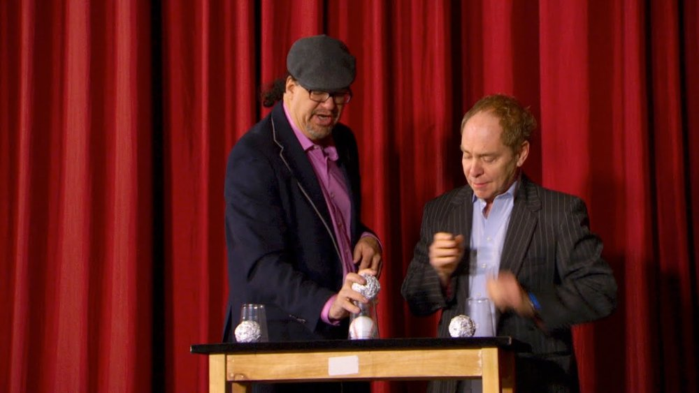 "Penn & Teller doing the ""Cups and Balls"" trick with clear plastic cups.  Source"