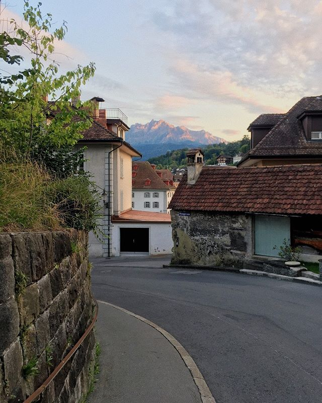 "One evening in Lucerne we wandered along a winding street towards the ancient city walls on a whim, hoping to make the climb before the historic site closed down for the night. – The incline steadily increased as the light was fading and since we were unfamiliar with the city, we thought we better turn around and try for another day. – We were a little disappointed with our luck but as we turned a certain corner on our way back down, this was the sight we were met with. The setting sun cast beautiful pastel hues over the mountain we visited just the day before. –  I don't think I fully appreciated it at the time since we were focusing on not getting lost in the dark, but I came across this photo on my phone later on and now it's one of my favourites from the whole trip. I do remember the brief moment of looking up, seeing all this and thinking to myself, ""oh gosh, I need to take a picture – this place doesn't even look like real life"". – Do you have any memories from a trip where something unexpected turned into a totally charming moment?"