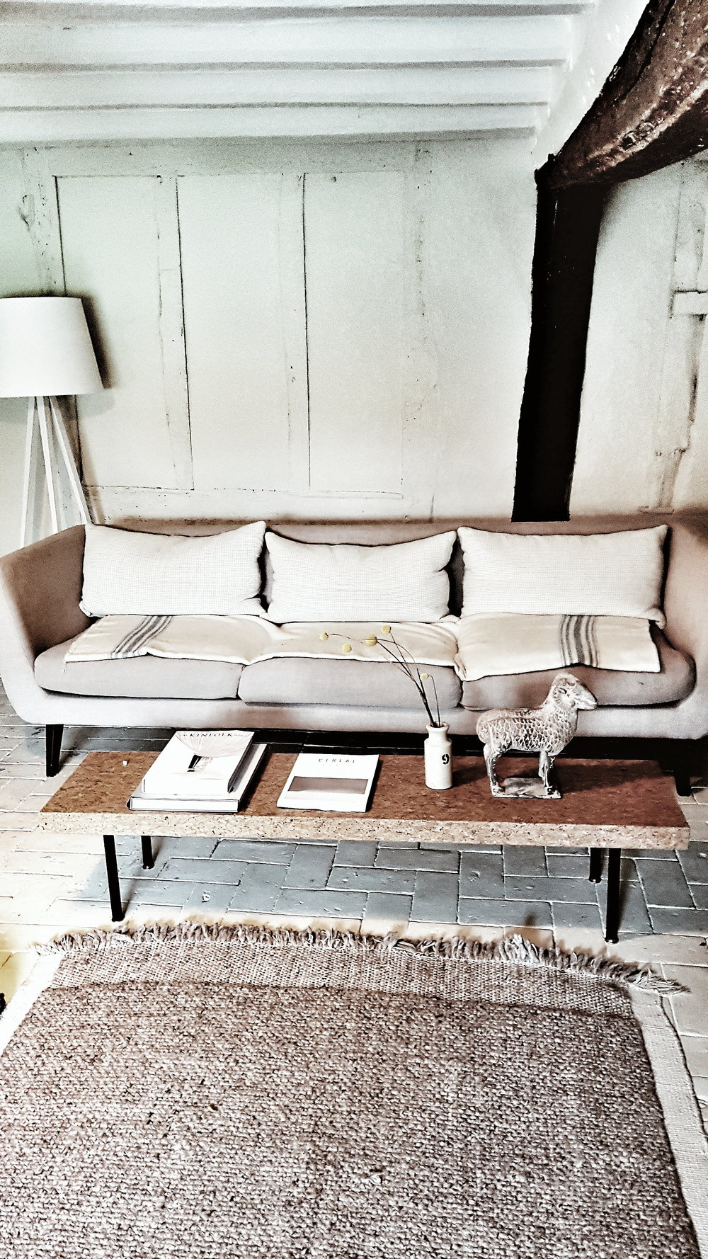 The living room at the cottage was painted in neutral colours with texture and warmth added through touches such as the jute rug and woolen cushions and blankets