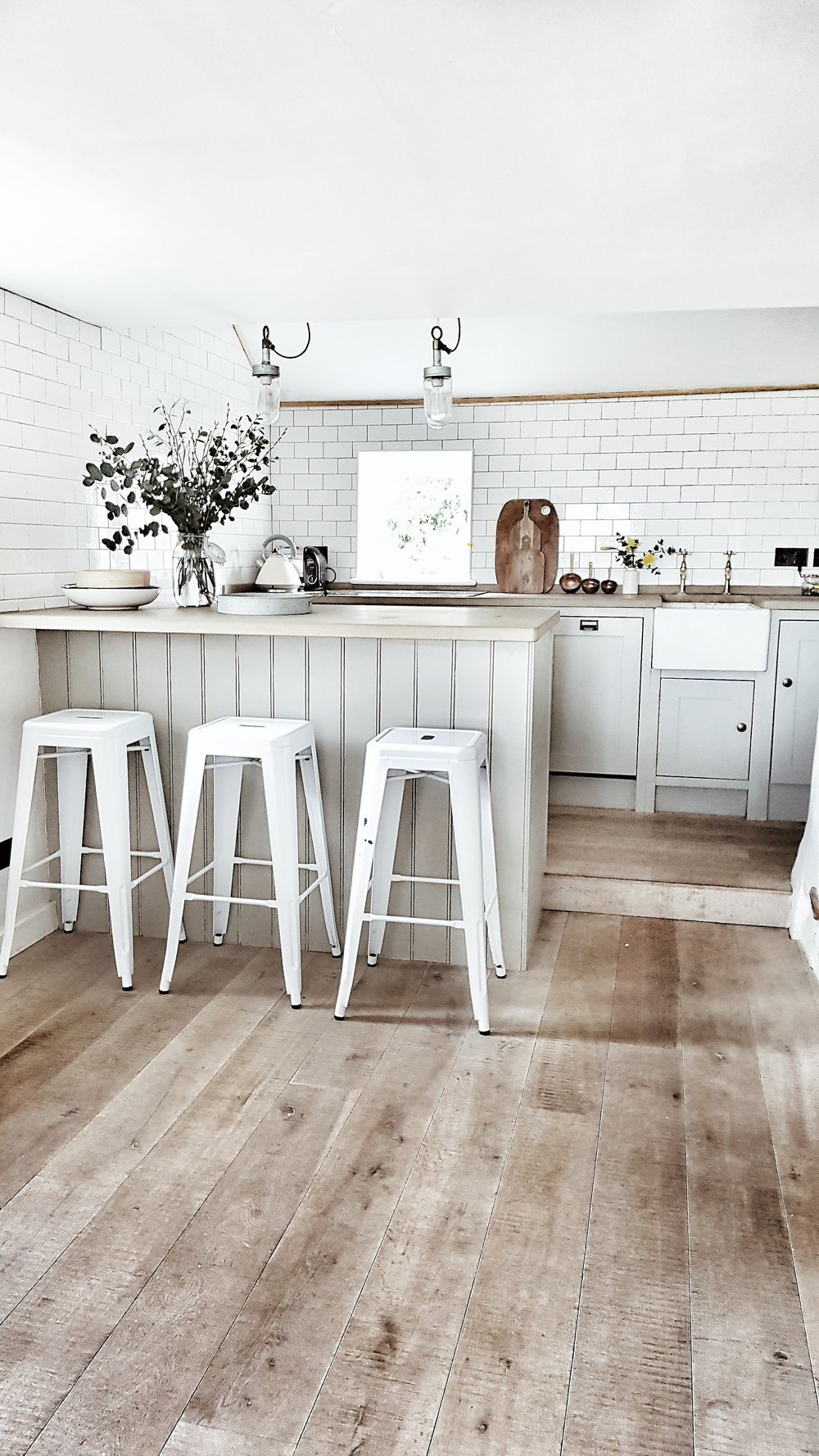 White metro tiles on the walls give the kitchen a contemporary feel that works with the medieval bones of the cottage
