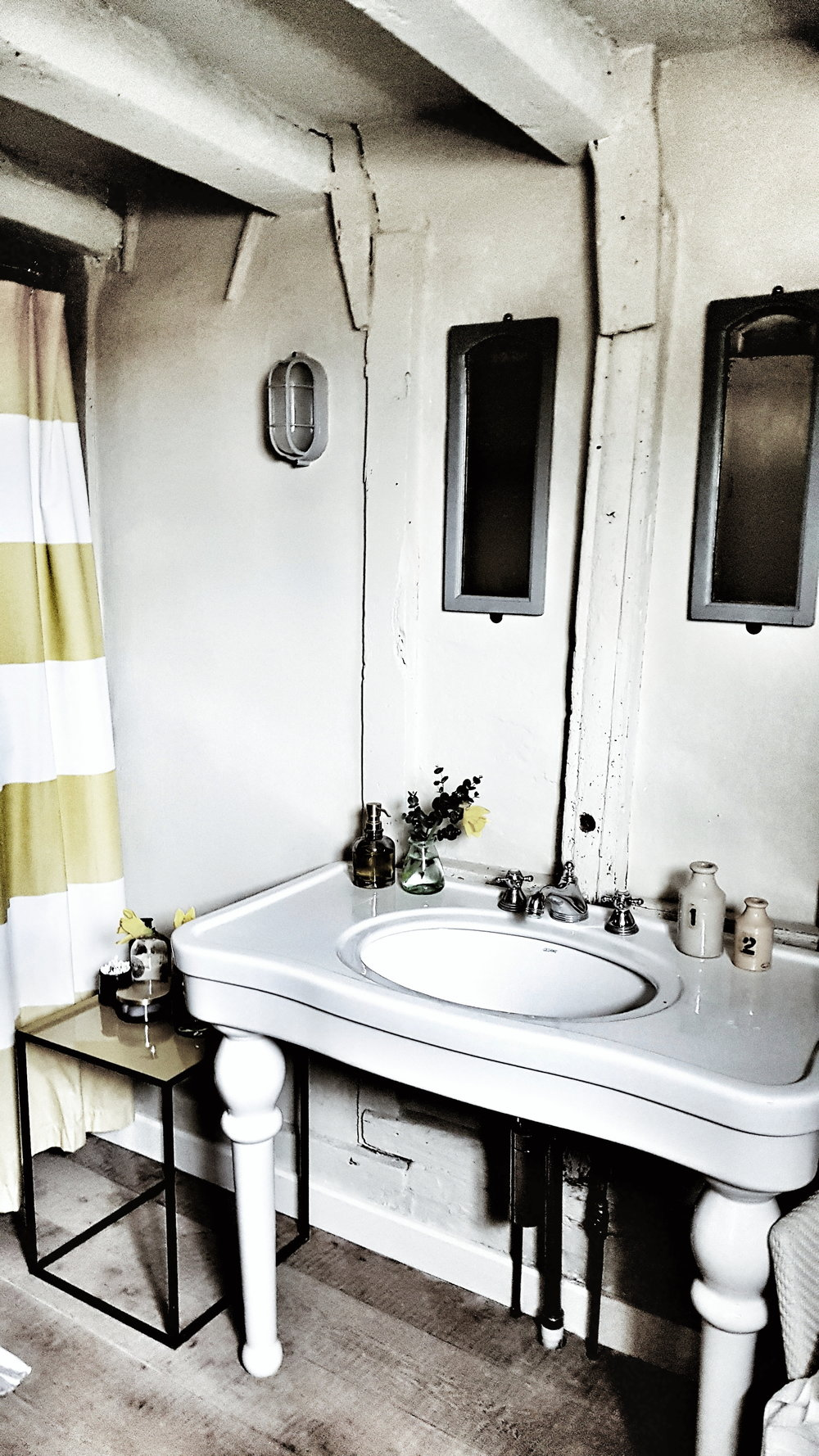The vintage sink and vanity area in the gorgeous rustic bathroom